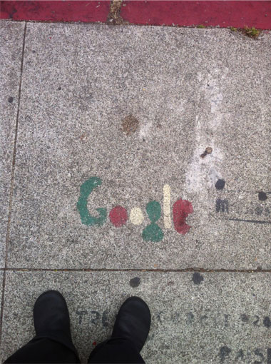 A marker painted on the pavement for a Google shuttle stop.